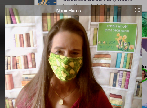 Nomi Harris, with a fake bookshelf backdrop and a pear facemask.