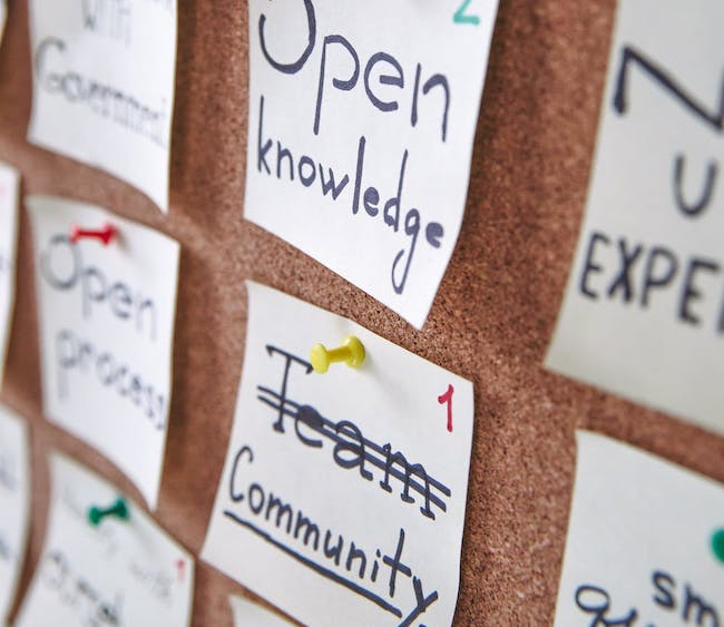 A corkboard with multiple posts pinned on it. Visible posts have keywords like open knowledge, community and open process.